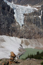 Rock cairn in front of angel glacier melting into sits which is cavell lake below jasper national park alberta ca Stock Images