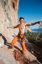 Rock climber collecting belay rope over the mountains handsome adult male blue sky and stock image Royalty Free Stock Photo