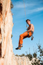 Rock climber hanging on belay rope over the mountains handsome adult male blue sky and stock image Stock Photos