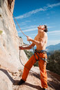 Rock climber holding belay rope over the mountains handsome adult male blue sky and stock image Stock Photography