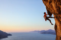 Rock climber resting while climbing cliff Royalty Free Stock Photo