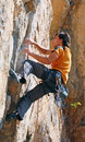The rock climber during rock conquest young man reaching sullit Stock Photo