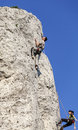 Rock climbers in action with blue sky behind Royalty Free Stock Image