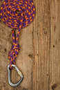 Rock climbing equipment gear with rope and connector on rustic wooden background often used for belay or abseiling by mountaineers Stock Images