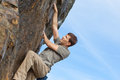 Rock climbing outdoors young healthy man or bouldering Stock Photo