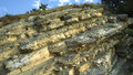 Rock deposits formed by sea and plates of white and yellow limestone coast landscape Stock Images
