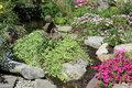 Rock and flower garden a with a statue in the center surrounded by water Stock Photo