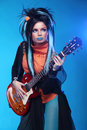 Rock girl plating on electric guitar on blue background studio Royalty Free Stock Photography