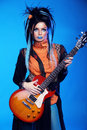 Rock girl posing with electric guitar playing hard rock on blue background Royalty Free Stock Images