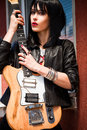 Rock girl young woman in style clothes with electric guitar outdoor shot Royalty Free Stock Image