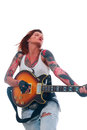 Rock n roll girl with tattoo portrait of young attractive lots of playing electric guitar taken against color background Royalty Free Stock Photos