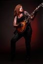 Rock n roll girl with tattoo portrait of young attractive lots of playing electric guitar taken against color background Stock Photos