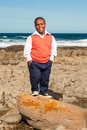 Rock posing dwarfish african man dressed in stylish clothes standing on a big on the shore with his hands in his pocket Royalty Free Stock Image