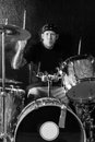 Rock and roll drummer photo of a playing his kit visible movement on the head arms drumsticks Royalty Free Stock Photos
