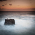 Rock in the sea at dusk and horizon Stock Photos