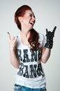Rock shouting girl pretty young emotional woman model with cute red haircut wearing white top ripped blue jeans black leather Royalty Free Stock Photography