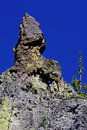 Rock spire with peek a boo cave and blue sky colorful against bright in crater lake national park Royalty Free Stock Images