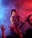 Rock star female singer and guitarist playing guitar at a concert Stock Photo