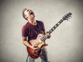 Rock star man acting like a with a guitar Stock Photography