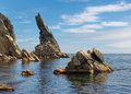 Rock sticking vertically out of the water Stock Photo