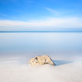Rock on a white sand beach and sea on horizon. Royalty Free Stock Image