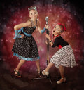 Rockabilly girls singing on a colorful background with glowing lights Stock Photography