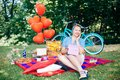 Group of friends at park having fun party. Beautiful girl with a gif in hands on a picnic Royalty Free Stock Photo