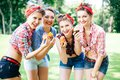 Group of friends at park having fun party. Cheerful girls with a cakes in hands. Retro style. Royalty Free Stock Photo