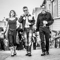 Rockabilly people festival th september porthcawl a group of walking a man is smoking a cigarette and they are all dressed in s Royalty Free Stock Image