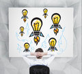 Rocket lamp on placard businessman looking to drawing Royalty Free Stock Image