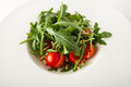 Rocket salad with cherry tomatoes and pine nuts served on white plate Stock Photography