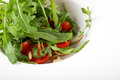 Rocket salad with cherry tomatoes and pine nuts served on white plate closeup Stock Photography
