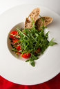 Rocket salad with tomato cherry and pine nuts served bread on white plate Stock Photography