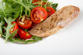 Rocket salad with tomato cherry and pine nuts served bread on white plate Stock Photos