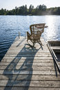Rocking chair on small lake dock wicker wooden in summer at casting long shadow Stock Photography