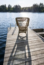Rocking chair on small lake dock wicker wooden in summer at casting long shadow Royalty Free Stock Photo