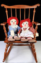 Rocking rag dolls in vintage child s chair on white carpet with black background Stock Images