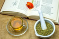 Rockrose tea with medieval textbook and flower Royalty Free Stock Photo