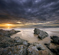 Rocks on beach with dramatic sky Stock Image