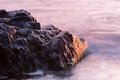 Rocks calm sea sunrise and at sunset or with purple color of water in marine or nautical background Royalty Free Stock Images