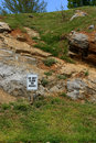 Rocks do not climb on sign planted in the grass in front of rocky ground Stock Images