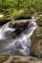 Between rocks ii waterfall landscape river flowing slowly in a forest Stock Image