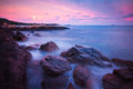 Rocks waves and the beautiful sunset coast Stock Image