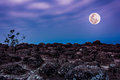 Rocky against blue sky and beautiful full moon at night. Outdoor Royalty Free Stock Photo