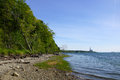 Rocky beach lined with trees on cousins island with large gas po power plant in the distance in yarmouth maine Royalty Free Stock Images