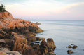Rocky coast of maine at dusk bass harbor lighthouse Stock Image