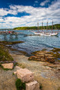 Rocky coast and view of boats in the harbor at bar harbor maine Stock Photography