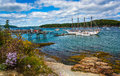 Rocky coast and view of boats in the harbor at bar harbor maine Royalty Free Stock Images