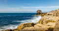 Rocky coastline with sea foam as the waves break onto the rocks this is the looking along the rocks toward pulpit rock which is Royalty Free Stock Image