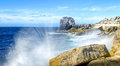 Rocky coastline with wave crashing against the rocks waves breaking onto this is looking along toward pulpit rock which is located Royalty Free Stock Images